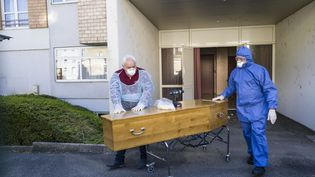 Des employés funéraires transportent le cercueil d'une victime du Covid-19 dans un Ehpad à Mulhouse (Haut-Rhin), le 5 avril 2020. (SEBASTIEN BOZON / AFP)