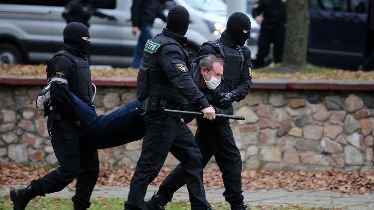 Des policiers portent un homme lors d'une manifestation de l'opposition contre le président AlexandreLoukachenko, à Minsk (Biélorussie), le 1er novembre 2020. (AFP)