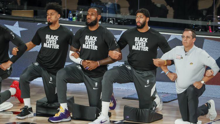 LeBron James (au centre) et ses coéquipiés des Los Angeles Lakers, posant un genou à terre, lors du match de reprise de la NBA, le 30 juillet 2020. (ERIK S. LESSER / EPA)