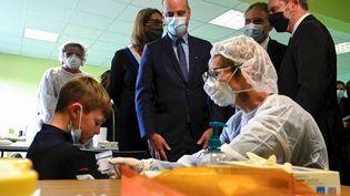 Jean-Michel Blanquer observe la réalisation d'un test salivaire avec un enfant, dans une école de Lavencourt (Haute-Saône), le 1er mars 2021. (SEBASTIEN BOZON / AFP)