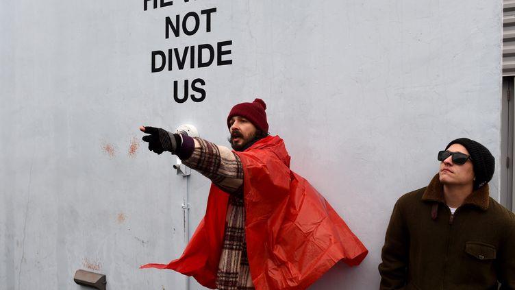 """Le comédien Shia LaBeouf sur le parvis du musée du Cinéma du Queens (New York), le 24 janvier 2017 à l'occasion de son projet """"He will not divide us"""". (TIMOTHY A. CLARY / AFP)"""