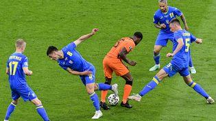 Wijnaldum entouré par plusieurs joueurs ukrainiens, le 13 juin à Amsterdam (OLAF KRAAK / POOL)