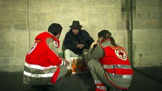 Des membres de la Croix Rouge discutent avec un sans-abri. (Photo d'illustration). (LIONEL BONAVENTURE / AFP)