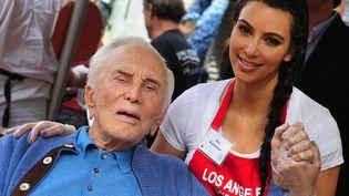 Fraîchement divorcée, Kim Kardashian en profite pour donner de sa personne en participant à une distribution de repas aux défavorisés de Los Angeles. Et le vieux monsieur n'est pas SDF, c'est Kirk Douglas! (FREDERIC BROWN / AFP)