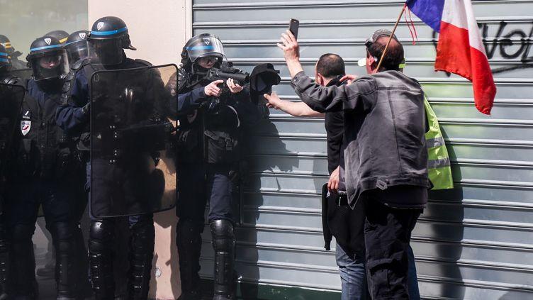 """Un policier pointe un lanceur de balles de défense (LBD) vers des manifestants lors d'une manifestation des """"gilets jaunes'', le 20 avril 2019 à Paris. (ZAKARIA ABDELKAFI / AFP)"""