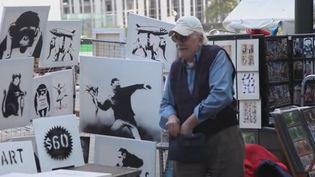 """L'artiste de rue Banksy, dont les oeuvres peuvent atteindre aux enchères des centaines de milliers de dollars, a installé un stand ce week-end près de Central Park, pour vendre une vingtaine de toiles """"authentiques et signées"""" pour... 60 dollars.  (DR)"""