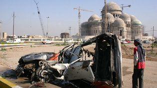 Un véhicule explosé à Mossoul, avec en fond une mosquée de la ville irakienne  (MUJAHED MOHAMMED / AFP)