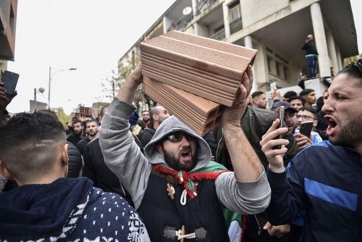 Un manifestant brandit des briques, à Tizi Ouzou le 8 décembre, pour contester la tenue de la présidentielle. (RYAD KRAMDI / AFP)