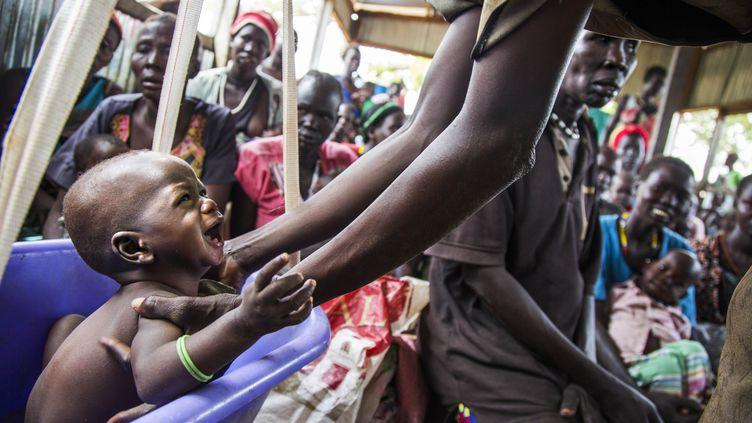 Une mère prend son enfant qui souffre de malnutrition, le 31 mai 2017, dans un centre de l'International Rescue Committee, àPanthau (Soudan du Sud). (ALBERT GONZALEZ FARRAN / AFP)