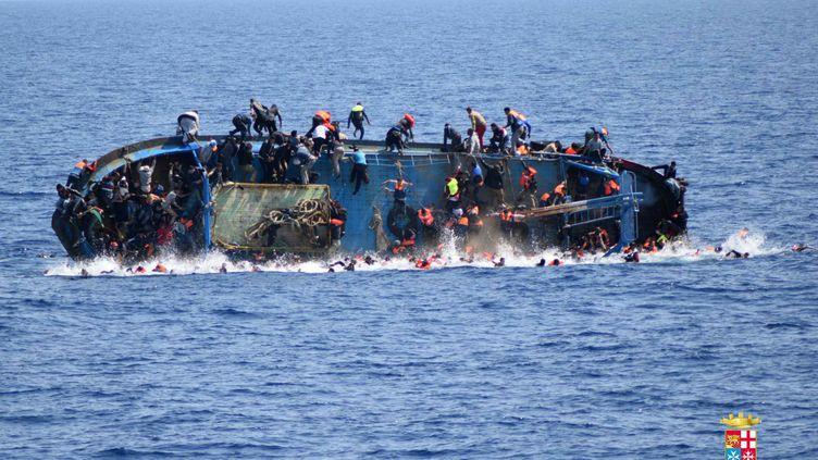 Photo communiquée par la marine italienne montrant des migrants tentant d'échapper au naufrage de leur navire, le 25 mai 2016 au large des côtes libyennes. (MARINA MILITARE / AFP)