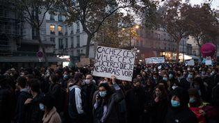 """Une manifestante brandit une pancarte lors d'une manifestation contre les violences policières et la proposition de loi sur la """"sécurité globale"""", à Paris, le 28 novembre 2020. (SEVERINE CARREAU / HANS LUCAS / AFP)"""