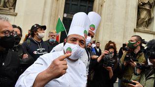 Desrestaurateurs se préparent à participer dans le centre de Rome, à une manifestation demandant l'assouplissement des restrictions de fermeture en raison du Covid-19,le 12 avril 2021. (ALBERTO PIZZOLI / AFP)