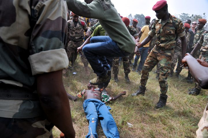 Un homme en civil saute à pieds joints sur un homme accusé d'être un ancien rebelle, le 5 février 2014 à Bangui (Centrafrique). (ISSOUF SANOGO / AFP)