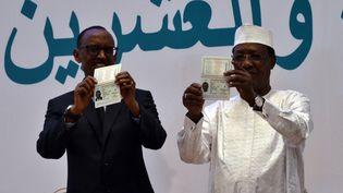 Les présidents du Rwanda, Paul Kagame (à gauche), et du Tchad, Idriss Deby, exhibent leur passeport panafricain à la tribune du 27ème sommet de l'Union africaine, le 17 juillet 2016, à Kigali, au Rwanda. (MINASSE WONDIMU HAILU / ANADOLU AGENCY)