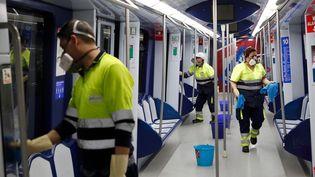Des agents de nettoyage dans le métro de Madrid, la capitale espagnole, le 10 mars 2020. (HANDOUT / COMUNIDAD DE MADRID / AFP)