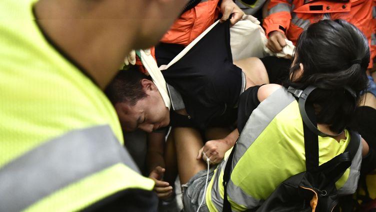 Unhomme pris en charge par les secours à l'aéroport de Hong Kong après avoir étéfrappé par des manifestants, mercredi 14 août. (ANTHONY WALLACE / AFP)