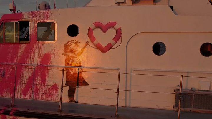 """Le graffiti de Banksy réalisé sur le navire """"Louise Michel"""", montrant une petite fille en gilet de sauvetage brandissant une bouée en forme de coeur. (HANDOUT  VIA REUTERS)"""
