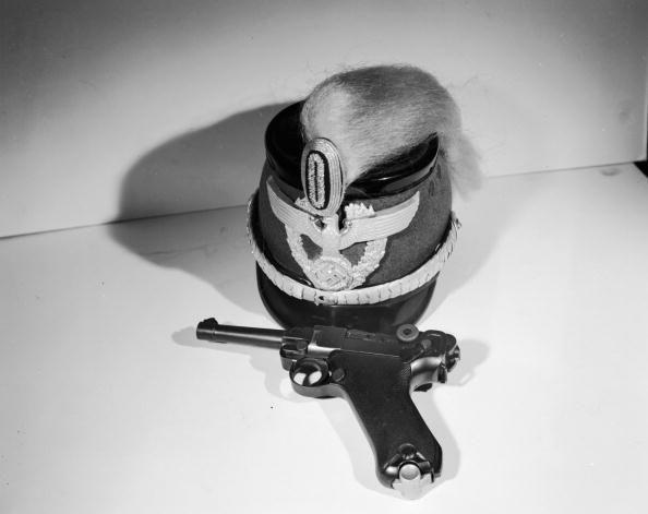 Un pistolet allemand Luger 9 mm accompagné d'une casquette nazie, photographiés en 1950. (ORLANDO / HULTON ARCHIVE / GETTY IMAGES)