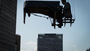 Le pianiste brésilien Ricardo de Castro Monteiro joue suspendu dans les airs à Sao Paulo (Brésil), le 6 mai 2012. (YASUYOSHI CHIBA / AFP)