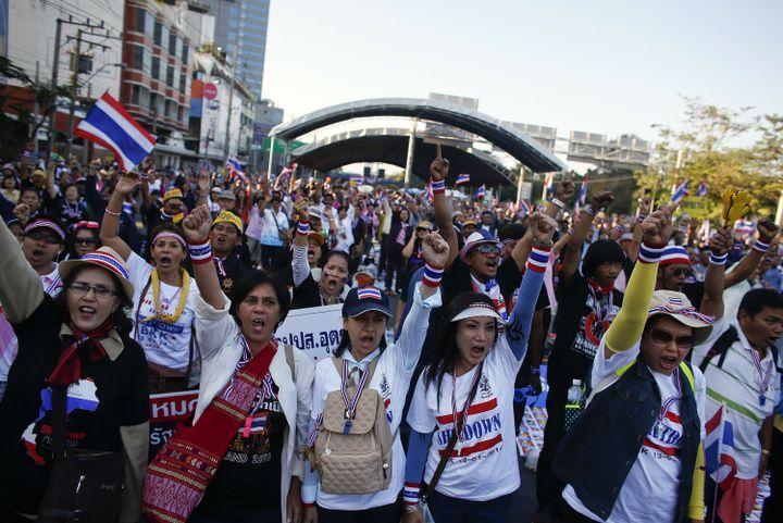 """Des manifestants arborant des tee-shirts """"Shutdown Bangkok"""" bloquent une intersection de la capitale thaïlandaise, le 13 janvier 2014. (ATHIT PERAWONGMETHA / REUTERS)"""
