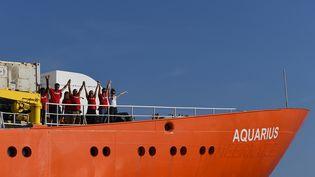 """Des membres d'équipage de l'""""Aquarius"""" sur le pont alors que leur navire quitte le port de Marseille, le 1er août 2018. (BORIS HORVAT / AFP)"""