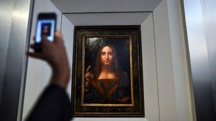 """Un journaliste prend une photo de l'oeuvre """"Salvator Mundi"""" de Léonard de Vinci récemment dévoilée à Christie's et estimée à 100 millions de dollars.  (JEWEL SAMAD / AFP)"""