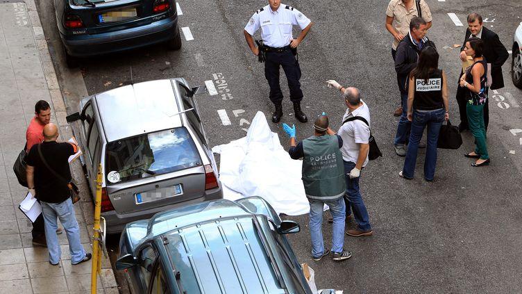 Des policiers autour du corps du braqueur abattu par un bijoutier, le 11 septembre 2013, à Nice (Alpes-Maritimes). (JEAN-CHRISTOPHE MAGNENET / AFP)