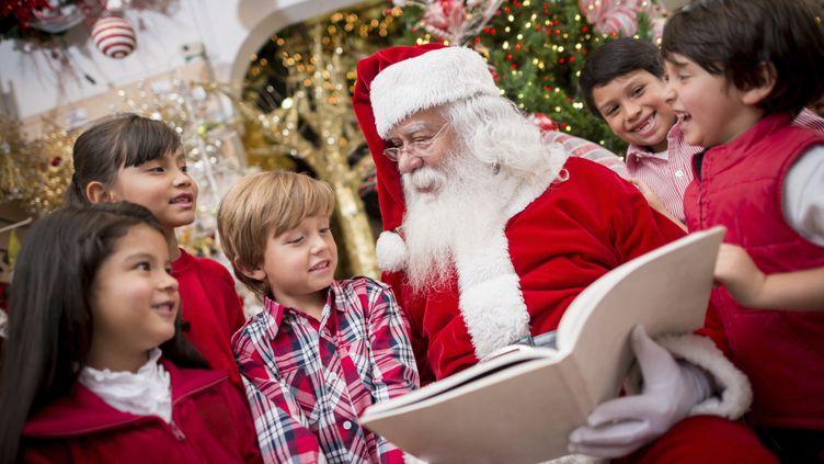 Des enfants entourent le père Noël à la veille des fêtes de fin d'année. (ANDRESR / E+ / GETTY IMAGES)