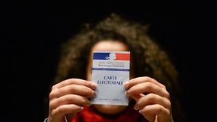 Une femme tient une carte d'électeur, à Besancon (Doubs), le 19 mars 2017. (SEBASTIEN BOZON / AFP)