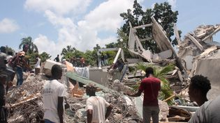 Des habitants devant des décombres dans la ville des Cayes, après le puissant séisme qui a frappé Haïti, le 14 août 2021. (STANLEY LOUIS / AFP)