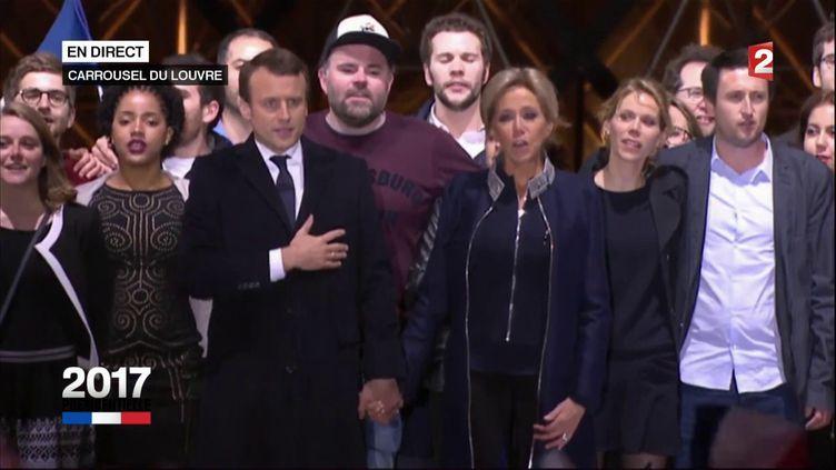 """Morgan Simon, au centre avec la casquette, chante la """"Marseillaise"""" avec Emmanuel Macron, devant la pyramide du Louvre, à Paris, le 7 mai 2017. (FRANCE 2)"""