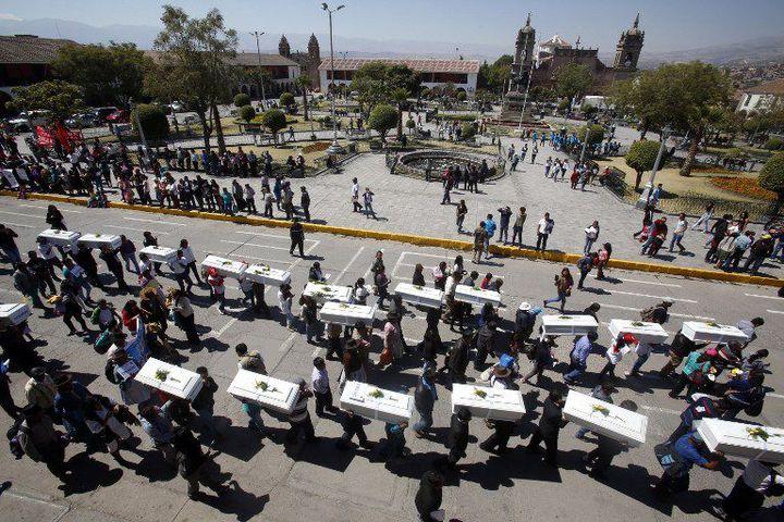 Dans la ville andine de Huamanga, le 15 août 2015, un cortège porteles cercueils de 60 civils tués lors du conflit armé entre l'Etat péruvien et le groupe maoïste Sentier lumineux (1980-2000). Les corps ont été exhumés entre 2011 et 2013. (MAX CABELLO / AFP)