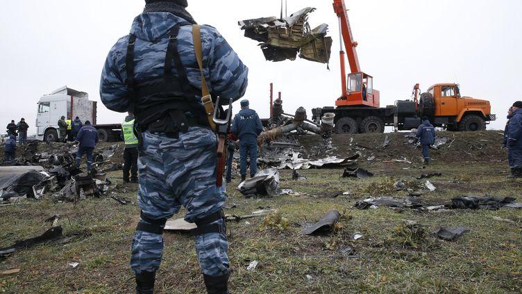 Un combattant séparatiste pro-russe regarde une grue porter l'épave du vol Malaysia Airlines MH17 abattu près du village de Grabové,dans la région de Donetsk (Ukraine), photo prise le 16 novembre 2014. ( MAXIM ZMEYEV / REUTERS )