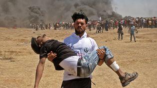 Un Palestinien porte un manifestant blessé, dans les affrontements avec les forces israéliennes, à la frontière entre Gaza et Israël, le 14 mai 2018. (MAHMUD HAMS / AFP)