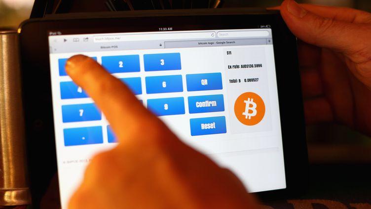 Un patron de pub utilise un iPad pour encaisser le paiement de ses clients en bitcoins, le 19 septembre 2013 à Sydney (Australie). (CAMERON SPENCER / GETTY IMAGES)