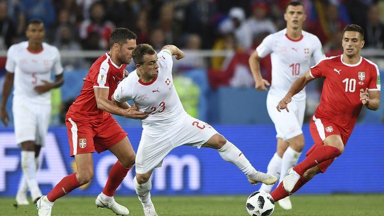 Le Suisse Xherdan Shaqiri accroché par le Serbe Dusko Tosic (OZAN KOSE / AFP)