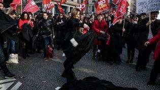 Une avocate du barreau de Lyon jette sa robe sur le sol pour protester contre la réforme des retraites, le 9 janvier 2020 à Lyon. (NICOLAS LIPONNE / HANS LUCAS / AFP)