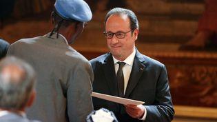 François Hollande salue un vétéran durant une cérémonie de naturalisation d'anciens tirailleurs sénagalais, à l'Elysée, le 15 avril 2017.  (GEOFFROY VAN DER HASSELT / AFP)