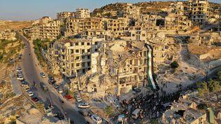 Unemanifestation anti-Bachar al-Assad sur les ruines d'un bâtiment qui a été touché lors d'un bombardement, dans la ville d'Ariha, dans la province d'Idlib, au nord-ouest de la Syrie,le 28 août 2020. (OMAR HAJ KADOUR / AFP)