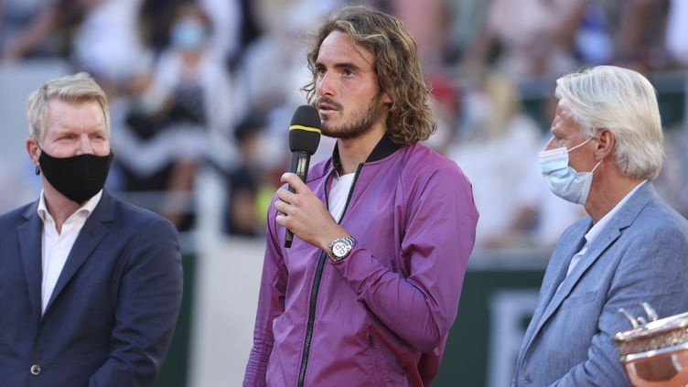 Stefanos Tsitsipas entouré deJim Courier (gauche) et Bjorn Borg(droite) lors de la cérémonie de remise de trophée de Roland-Garros le 13 juin 2021. (JEAN CATUFFE / DPPI via AFP)