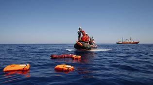 Des membres de Médecins sans frontières effectuent un sauvetage, le 23 juin 2018, au large de la Tunisie, non loin de l'île italienne de Lampedusa. (PAU BARRENA / AFP)