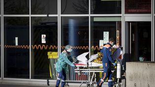 Des soignants transportent un malade atteint du Covid-19 au CHU de Strasbourg (Bas-Rhin), le 31 mars 2020. (ELYXANDRO CEGARRA / ANADOLU AGENCY / AFP)