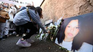 Une jeune femme dépose des roses blanches devant le collège Jean-Henri Lambert, lors d'une marche blanche à Mulhouse (Haut-Rhin), le 24 octobre 2021. (FREDERICK FLORIN / AFP)