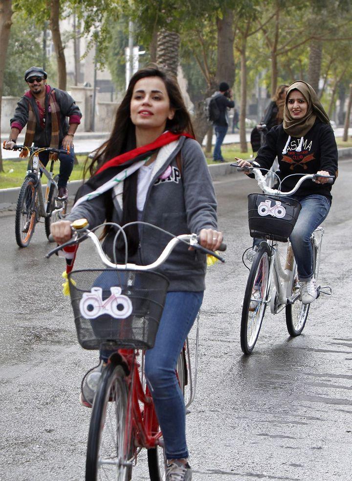 L'artiste cycliste irakienne, Marina Jaber, sur son désormais fameux vélo rouge, entre la rue Abou Nawas et le pont suspendu dans le quartier commerçant de Karrada, pour une manifestation contre le conservatisme et pour la paix, le 5 décembre 2016, à Bagdad. (SABAH ARAR/AFP)