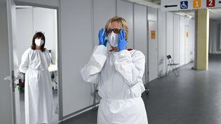 Une soignante s'équipe dans un centre de vaccination deHeuchelheim (Allemagne), le 21 janvier 2021. (ARNE DEDERT / DPA / POOL / AFP)