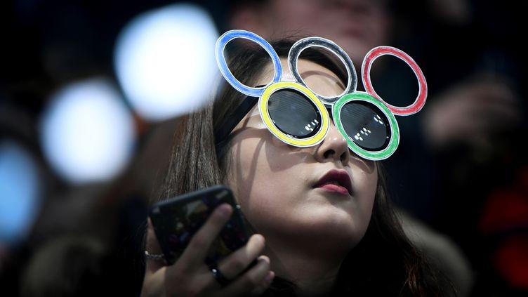 Une spectatrice regarde une épreuve des Jeux olympiques de Pyeongchang (Corée du Sud), le 20 février 2018. (WANG ZHAO / AFP)