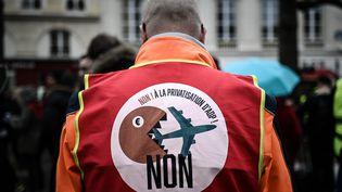 """Un militant de la CGT manifeste contre la privatisation du groupe Aéroports de Paris, dans un rassemblement de """"gilets jaunes"""", à Paris, le 13 mars 2019. (PHILIPPE LOPEZ / AFP)"""