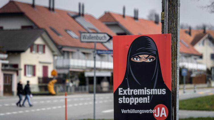 """Une affiche en faveur du """"oui"""" à l'initiative interdisantde se couvrir le visage dans les lieux publics, le 7 mars 2021 à Biberen (Suisse). (FABRICE COFFRINI / AFP)"""