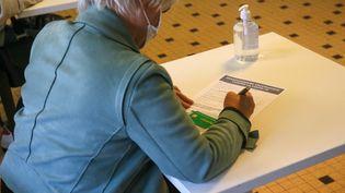 Une femme remplit unquestionnaire avant de se faire vacciner contre le Covid-19, à Valence (Drôme), le 3 mai 2021. (NICOLAS GUYONNET / AFP)