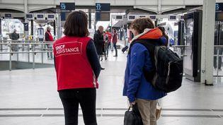 Une employée de la SNCF aide une voyageuse à lagare de Lyon, à Paris, le 13 avril 2018, jour de grève au sein du groupe. (DAVID SEYER / AFP)